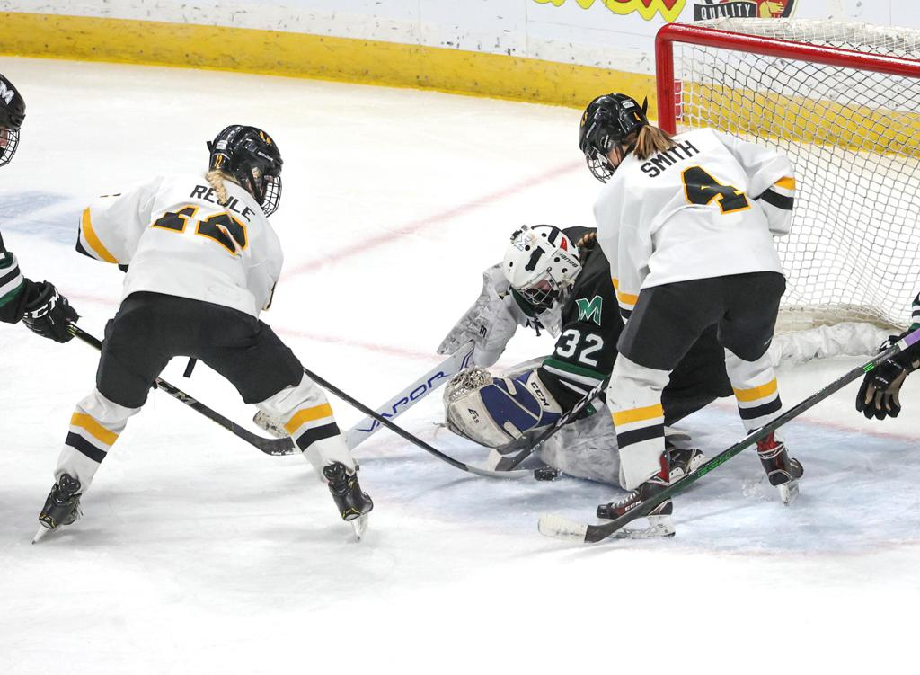 Proctor/Hermantown goaltender Abby Pajari (32) makes a save in the second period under pressure from Warroad's Abbey Reule 912) and Reanna Smith (4).  Photo by Cheryl A. Myers, SportsEngine