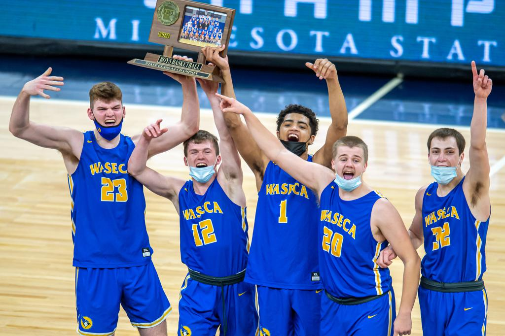 Waseca's Andrew Morgan (23), Ryan Dufault (12), Tyreese Willingham (1), Zach Hoen (20) and Matt Seberson (32) celebrate with the Class 2A trophy.  Target Center, Class 2A championship Waseca vs. Caledonia  April  10, 2021   Photo by Earl J. Ebensteiner, SportsEngine